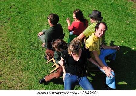 Six friends playing the game musical chairs - two are trying to fit on one chair, and another is falling off his little chair. - stock photo