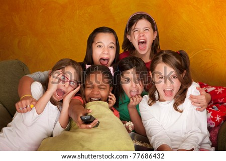 Six girls watching a movie scream at a sleepover - stock photo