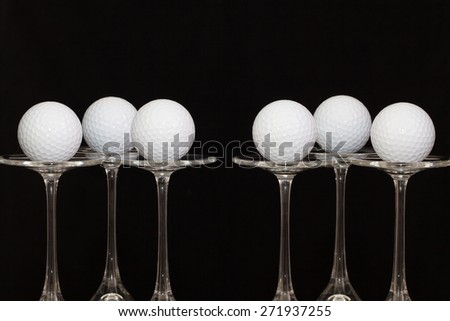 Six glasses of champagne with golf balls