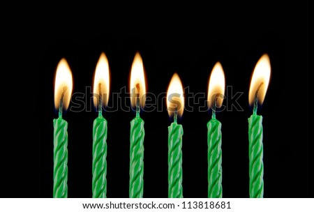 Six green burning candles on black background
