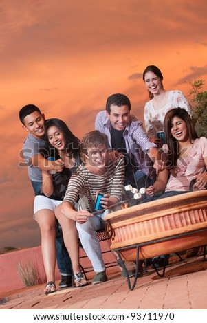 Six happy teens roast marshmallows over hot pot - stock photo