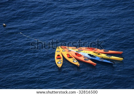 Six kayaks tied together floating in the sea