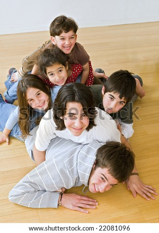 six kids in different ages piled on each other on the floor - stock photo