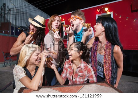 Six laughing people with slices of pizza outdoors - stock photo