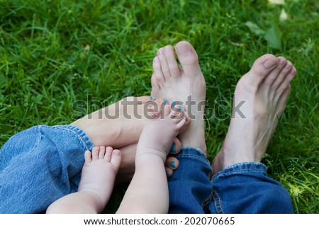 Six legs feet in grass, father's dad's mum's mother's boy's baby's, family concept - stock photo