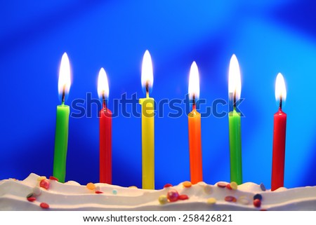 Six lit birthday candles close up, shallow dof