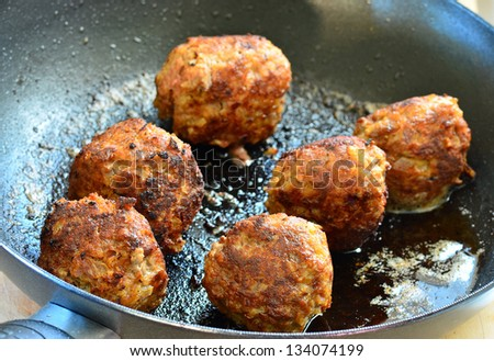 Six meatballs in frying pan being prepared for sandwiches.  Strong back light. - stock photo