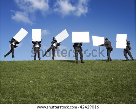 Six men on the crest of a grassy hill, carrying blank white signs or boards. - stock photo