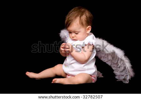 six month baby angel over black background