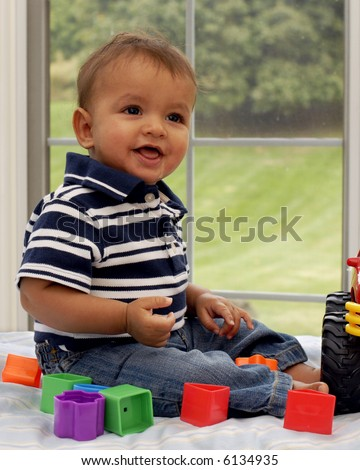 Six-month boy with his toys in front of a big window.