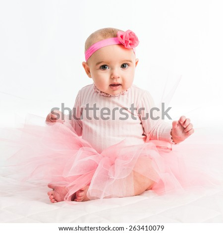 six-month girl in a pink skirt on a white background - stock photo