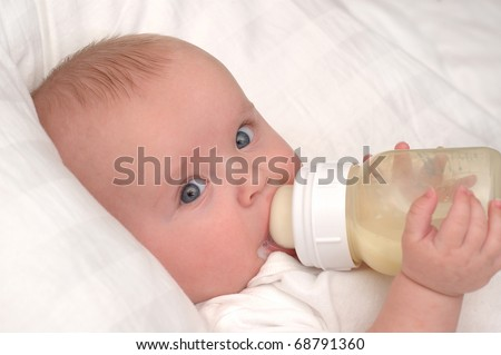 Six month old baby boy drinking his bottle - stock photo