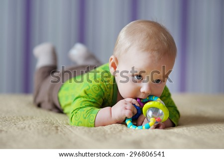Six month old baby play with bright toy - stock photo