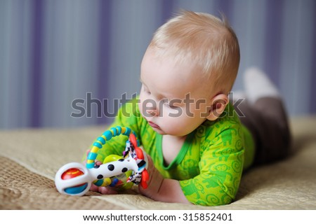 Six month old baby play with bright toys  - stock photo