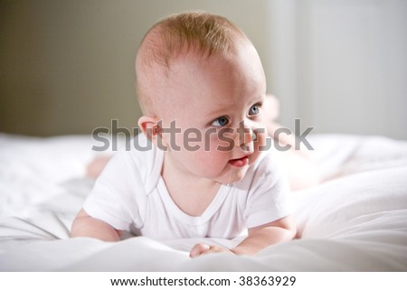 Six month old baby with staring with blue eyes - stock photo