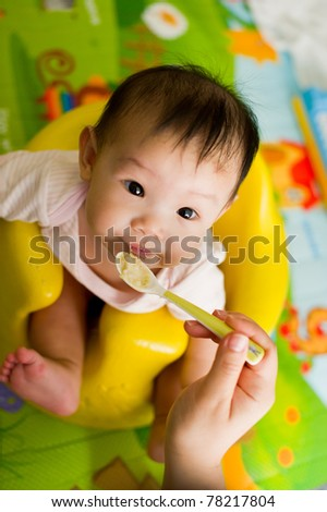 Six month old South East Asian Chinese baby girl sitting in a yellow seat, being spoon fed - stock photo