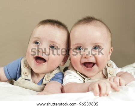 Six month old twin boys laughing and smiling - stock photo