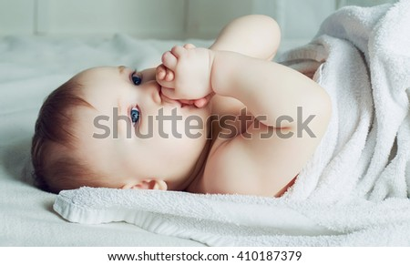 six months old baby with a towel after taking a bath, in bed at home - stock photo