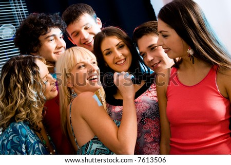Six people listen to singing of their girlfriend at a karaoke party - stock photo