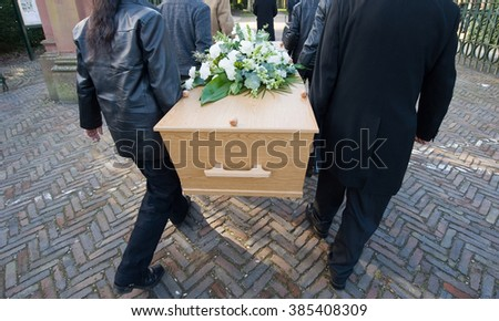 Six peoply are carrying a coffin on to a cemetery - stock photo