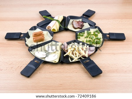 Six raclette pans with edam cheese and ham, bacon, mushroom, spring onion, coctail sousages on wooden table - stock photo