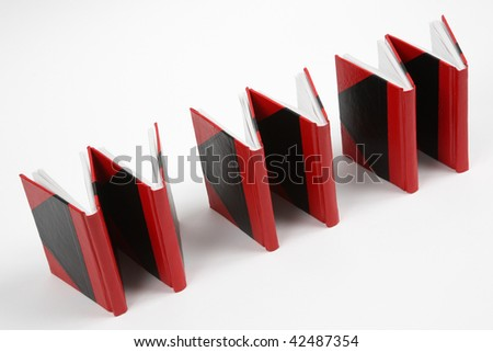 Six red and black books positioned so that they form the letters 'www' against a white background. Tilted shot. - stock photo