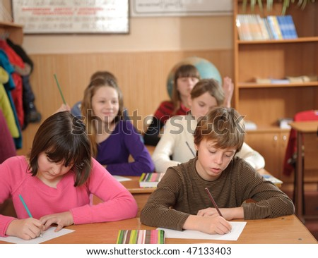 Six schoolchildren are writing during lesson in elementary school - stock photo