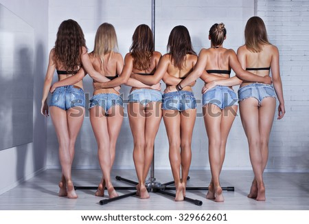 Six slim sexy pole dance women team backside view in white interior