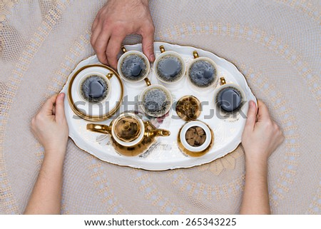 Six Small Cups of Turkish Coffee on a Tray Hold by Hand on Top of a White Table in High Angle View. - stock photo