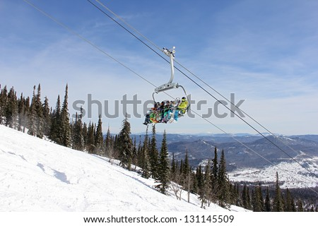six snowboarders ride the lift on a background of mountains, Russia, Sheregesh(Kemerovo Region), 2013 - stock photo