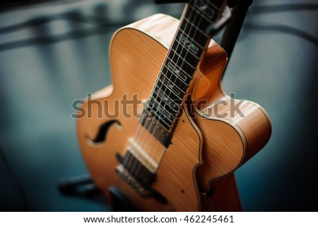 six-string acoustic guitar on a stand
