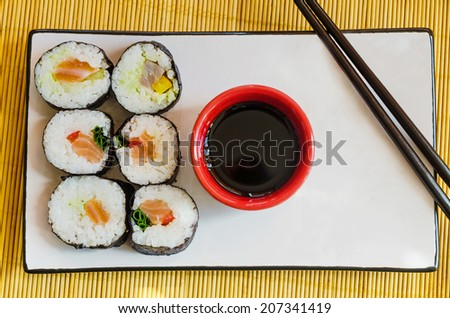 six sushi rolls on a  plate with a bowl of soy sauce and chopsticks - stock photo