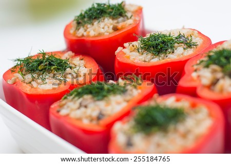 Six tasty appetizing peppers stuffed by rice mix with champignons, carrot and onion - stock photo
