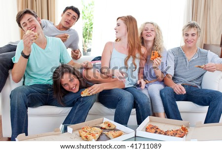 Six teenagers eating pizza in the living-room on the sofa - stock photo