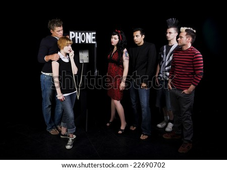 Six teenagers in a high school play.  A group of teenagers wait for their turn to use a public phone, while another girl hogs it. - stock photo