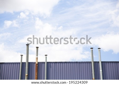 Six ventilation pipes over blue sky closeup on industrial place