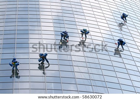 Six washers wash the windows of modern building