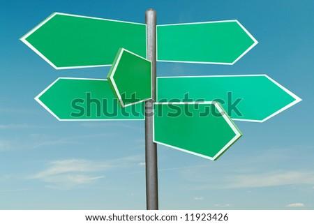 Six-way green blank roadsign over blue sky - stock photo