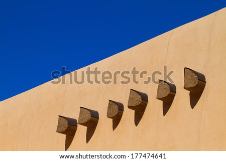 Six wooden beams, called vigas, extend from the walls of a traditional-style building in Santa Fe, New Mexico - stock photo