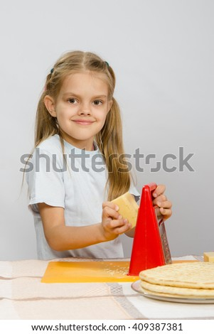 Six-year girl posing at the kitchen table with cheese and a grater in the hands of