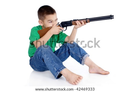 six-year-old boy aiming a toy rifle in a seated shooting position, isolated on white background - stock photo