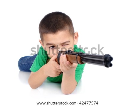 six-year-old boy aiming a toy rifle, lying in prone shooting position, isolated on white background - stock photo