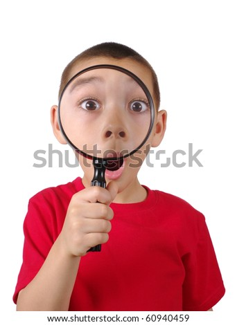 Six-year-old boy amazed looking through a magnifying glass, with mouth open, isolated on pure white background