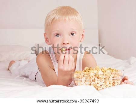 six year old boy boy eating popcorn in bed at home - stock photo