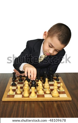 Six year old boy making a chess move, isolated on white background - stock photo