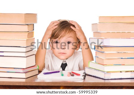 Six year old boy surrounded by piles of books isolated against a white background