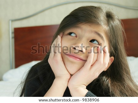 Six year old girl chin on hands thinking while lying down on bed