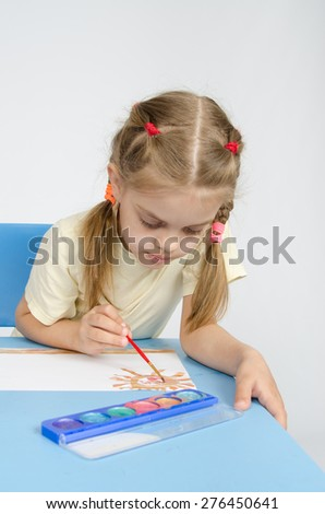 Six year old girl sitting at the table and draws paints