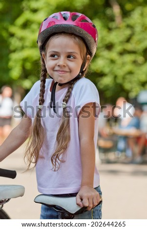 Six year old girl with bicycle wearing a bike helmet - stock photo