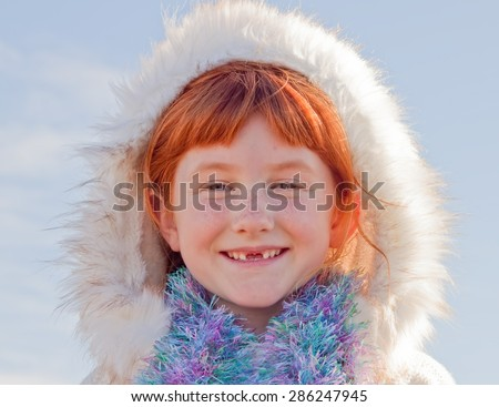 six year-old red haired girl with two front teeth missing and wearing Eskimo style fur lined hood - stock photo